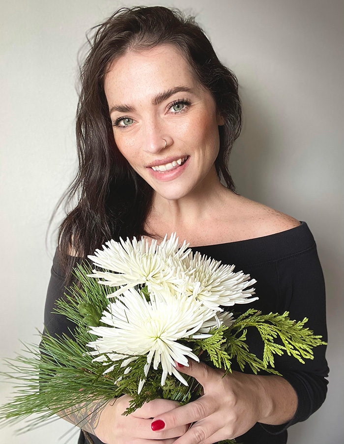 WeedMD Communications Manager, Victoria Dekker holding a bouquet of flowers